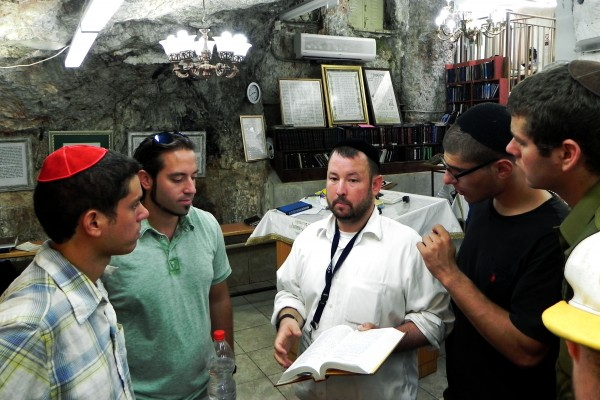 TORAH: Learning the famous Mishnah of Pirkei Avos. Rabbi Ben Packer, Director of the Jerusalem Heritage House teaches some Pirkei Avos by the tomb of Shimon Hazadik a sage that's quoted in the texts. Guests from the Jerusalem Heritage House Listen attentively.