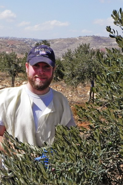 Matt Glassman staff of Heritage House harvesting olives near Efrat in Judea and Samaria.