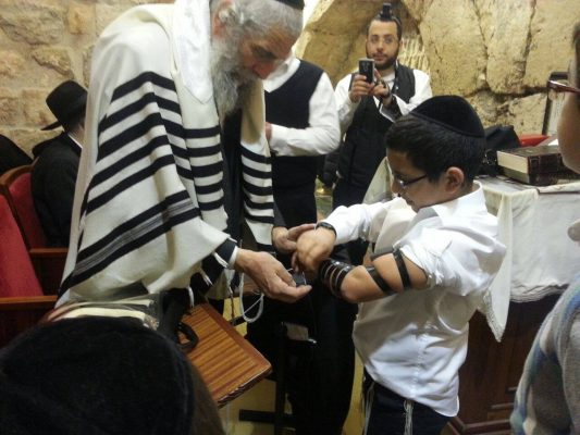 A Young boy's first time putting on tefillin!