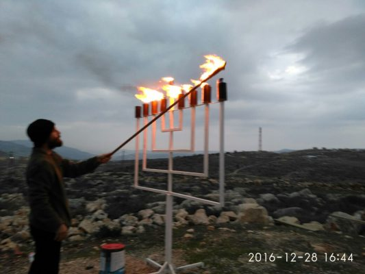 Lighting of the Menorah outside of renovated synagogue in West Kfar Tapuach